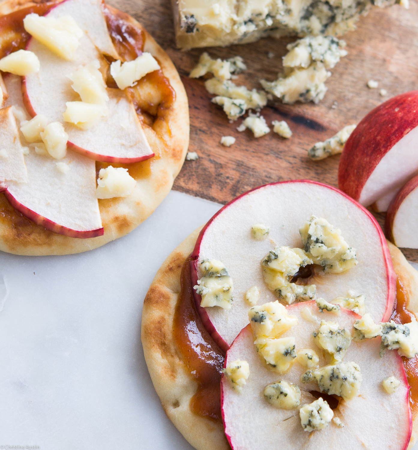 Naan flatbreads with apple butter and Dijon mustard topped with thinly sliced apples, Stilton cheese or cheddar cheese.